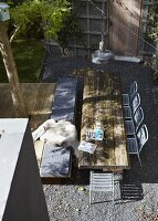 View down onto table made of rustic wooden timbers and metal terrace chairs on gravel floor in sunny urban garden