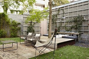 Seating area on terrace with wooden decking and butterfly chair in urban garden