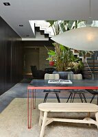 Simple wooden bench and retro, metal dining table below designer pendant lamp in open-plan interior