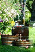 Mini-Teiche in Holzfässern mit Papierschiffchen für ein Gartenfest