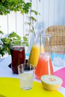 Fruit juice drinks cooled with ice cubes in glass decanters on summery garden table set with bright colours