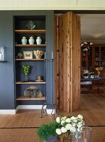 Integrated shelving in niche of wood-panelled wall next to doorway with wooden folding door