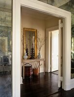 Open doorway with white, moulded frame and view of console table and mirror