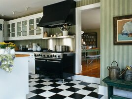 Modern country house kitchen with chequerboard patterned floor and open door looking into dining room