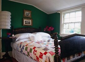 Vintage wooden bed with patchwork bedspread against green-painted wall
