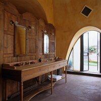 Long, wooden washstand against wooden screen in Mediterranean bathroom