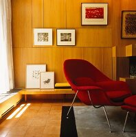 Interior with red, retro armchair and footstool and wood-panelled walls