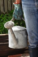 A woman carrying a watering can in the garden