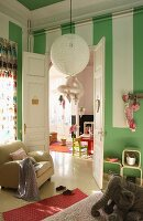 Child's bedroom with green and white striped walls and double doors leading to playroom