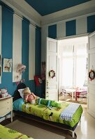 Blue walls with white stripes in child's bedroom with twin beds
