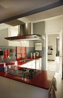 Modern L-shaped kitchen with red worksurfaces and protective grid around hob