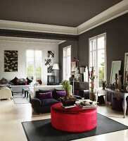 Ottoman with red velvet upholstery, sofa set and tall windows in elegant salon