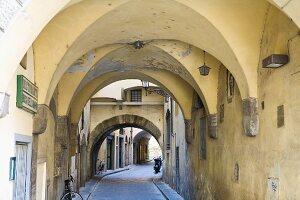 Vaulted arcades in Italian alleyway