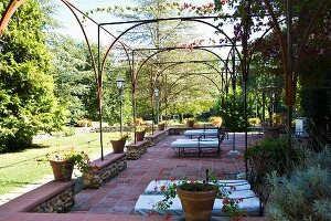 Spacious terrace with pergola of delicate metal struts in Mediterranean garden