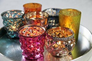 Colourful glass tea light holders on tray