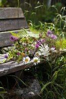 Bouquet of wild flowers on garden bench