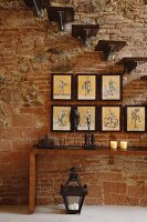 Wall console table, collection of pictures and cantilevered stairs in front of a rustic brick wall