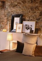 Decorative pillows on a bed and table with pictures in front of a natural stone wall