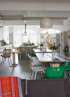 Loft-style interior with several tables and various chairs in front of open-plan kitchen