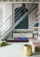 Steel staircase in front of arched niche in wall and colourful floor cushions in corner of loft-style living room