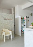 Loft-style interior - white-painted, vintage wooden chair against partition installation and masonry shelving in open-plan kitchen