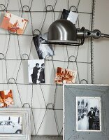 Photos on metal mesh pinboard hanging on wall and retro lampshade