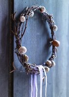 Wreath decorated with snail shells hanging on wooden wall