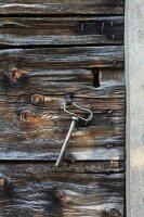 Old chapel key hanging on hook on wooden door