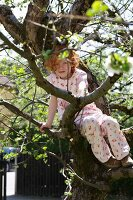Girl sitting in a tree in garden