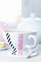 Teacup with home-made decoration of snowflake-patterned and black striped tape