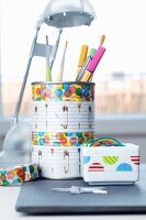 Storage pot for pens and paintbrushes made from tin can and china pot of rubber bands both decorated with patterned tape