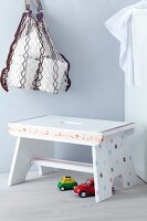 Foot stool decorated with prettily patterned tape, colourful toy cars on floor and net shopping bag hanging on wall