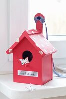 Romantic, pink bird box with label reading 'Sweet home' and tape spots