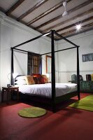 Four-poster bed with black frame on red floor in minimalist bedroom with wood beam ceiling