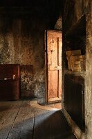Light falling through half-open wooden door in room of old house with sooty walls