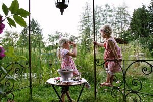 Two blonde girls with cherries in garden pavilion