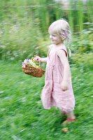 Blonde girl running through garden with basket of flowers