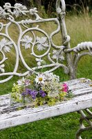 Posy of wild flowers on garden bench