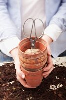 Hands holding plant pots with twine and scissors