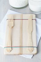 Rubber bands stopping cutlery slipping from breakfast board