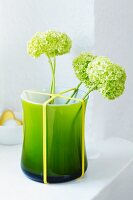 Green vase with rubber band holding flowers in place