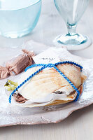 Small present: scallop shells filled with sweets and tied with cord holding name card