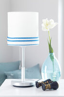 Table lamp decorated with cord, tulip in glass vase and binoculars