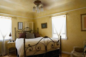 Naturally lit bedroom with decorative iron bed.