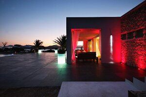 Red lights illuminating outdoor seating area at dusk