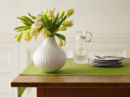 Fresh Flowers in a White Vase on a Table with a Green Table Runner