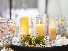 Candles and flowers on silver plate and glasses painted with flowers