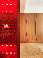 Red plastic wine rack and wood-panelled walls in background
