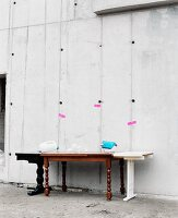 Antique wooden table with mismatched table elements added on against concrete wall