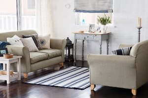 Blue and white accents in inviting seating area with two sofas and small vintage desk